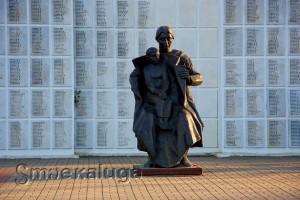 Женщина с ребенком на руках на фоне Стены памяти калуга
